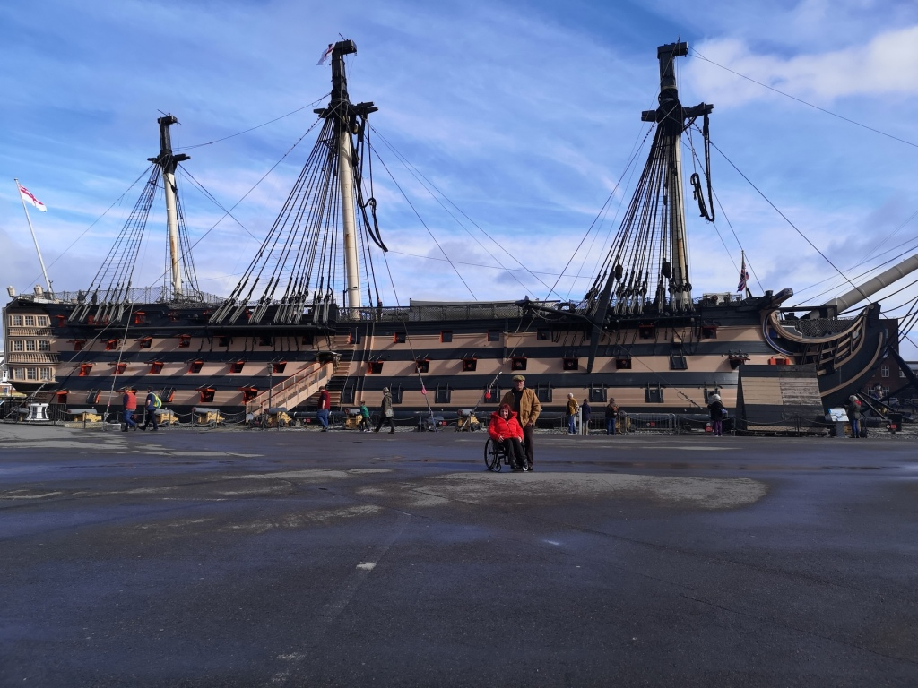 Lucy and her Dad stood in the Dockyard with HMS Victory behind them