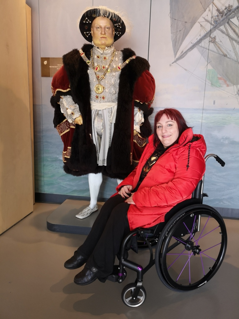 Lucy sat infront of a statue of Henry VIII she is in her wheelchair wearing a red coat
