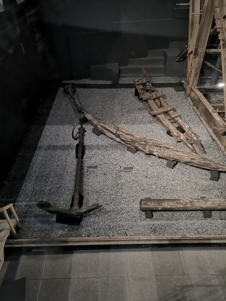 The Anchor of the Mary Rose lies on a grey floor, wooden pieces of the ship can be seen to the left of the anchor